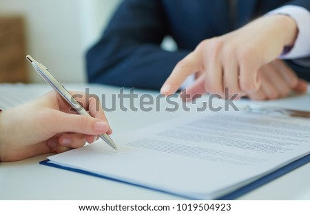 Young smiling businessman proposes to sign the contract.  Woman signing a loan agreement. Photo with depth of field.