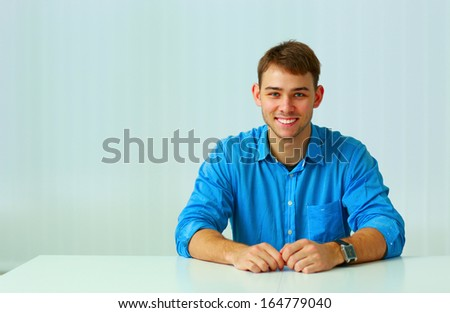 Young smiling businessman sitting at the table in office
