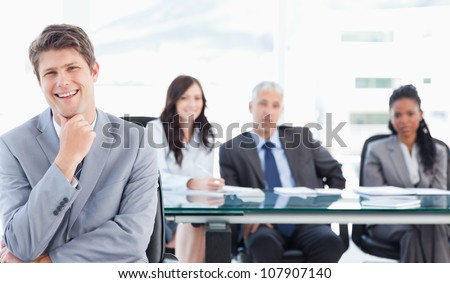 Young smiling businessman sitting in front of his team with his hand on his chin