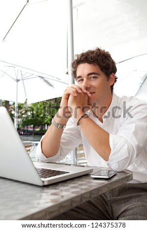 Young smiling businessman sitting with his laptop computer at a coffee shop terrace, with his hands together and his fingers interlinked, outdoors.