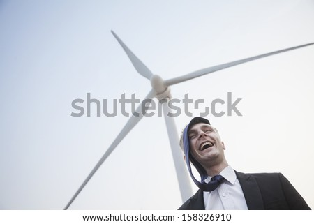 Young smiling businessman standing beside a wind turbine