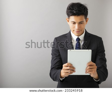 young smiling businessman watching the tablet pc - stock photo
