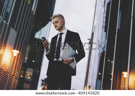 Young smiling businessman wearing black suit and using modern smartphone with laptop while standing near skyscraper outdoors, successful manager using his cellphone while working in modern office - stock photo