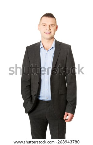 Young smiling businessman with hand in pocket. - stock photo