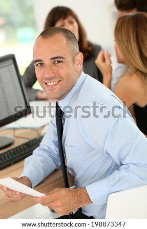 Young smiling businessman working on desktop computer
