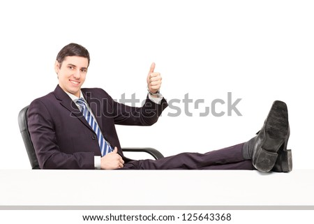 Young smiling businessperson sitting on a chair with his legs up and giving a thumb up isolated on white background - stock photo