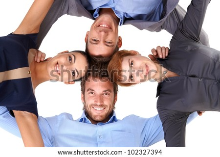 Young smiling businessteam embracing, view from below.