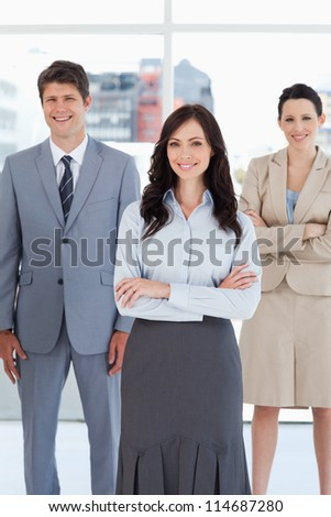 Young smiling businesswoman crossing her arms in front of two relaxed colleagues - stock photo