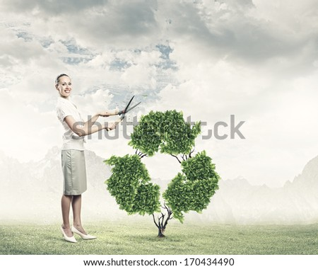 Young smiling businesswoman cutting plant in shape of recycle sign