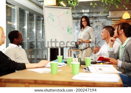 Young smiling businesswoman explaining graph to his colleagues - stock photo