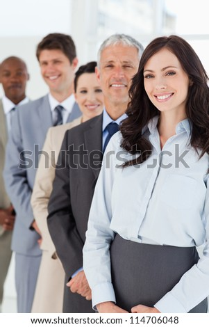 Young smiling businesswoman looking confident while being followed by her colleagues