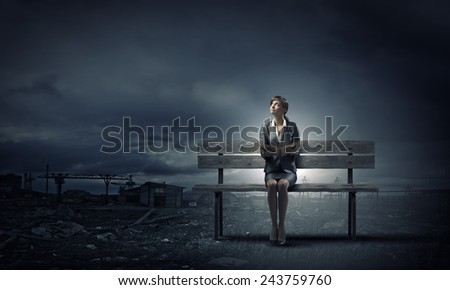 Young smiling businesswoman sitting on bench with book in hands - stock photo