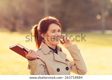Young smiling businesswoman,student professional outdoors in a city park talking on cell smart phone and  holding a red journal.Businesswoman smiling,Life style, - stock photo