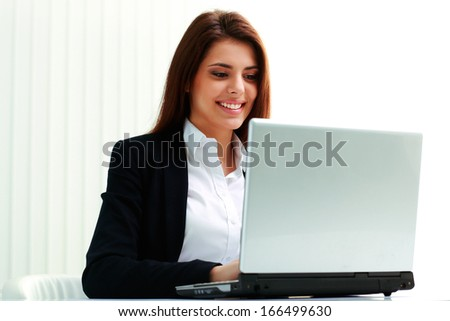 Young smiling businesswoman typing on the laptop in office - stock photo