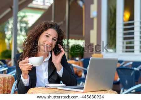 Young smiling businesswoman working at an outdoor cafe as she enjoys coffee while chatting on her mobile phone with her laptop open in front of her - stock photo
