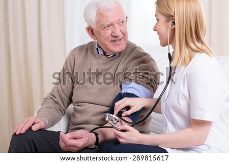 Young smiling caregiver checking her older patient's hypertension