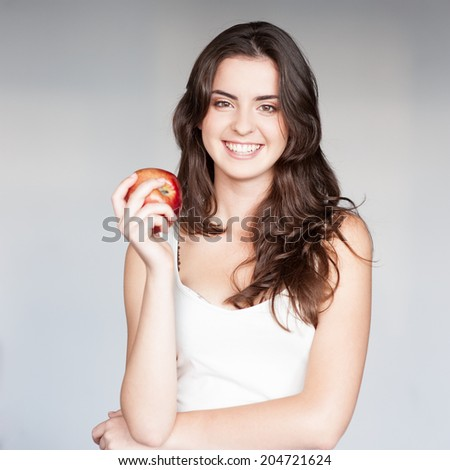 young smiling casual caucasian brunette  woman in white singlet holding red apple over gray background - stock photo