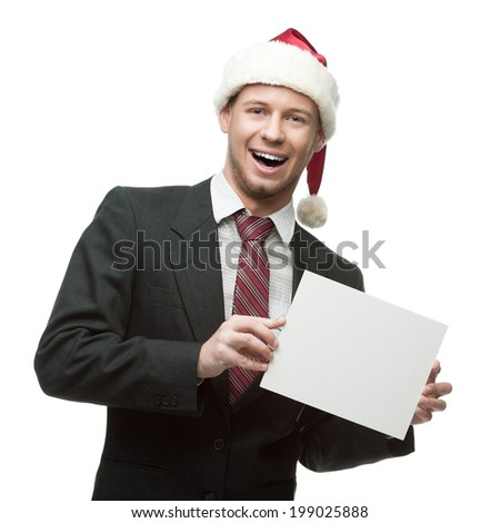young smiling caucasian businessman in black suit and santa hat holding sign isolated on white - stock photo
