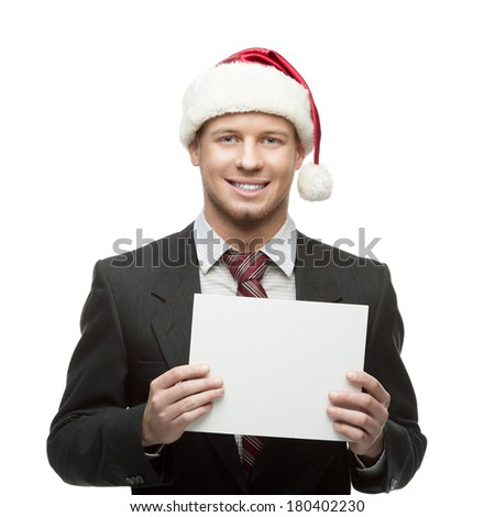 young smiling caucasian businessman in black suit and santa hat showing thumbs up isolated on white - stock photo