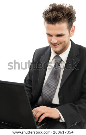 Young smiling Caucasian man working on laptop indoors over white background. - stock photo