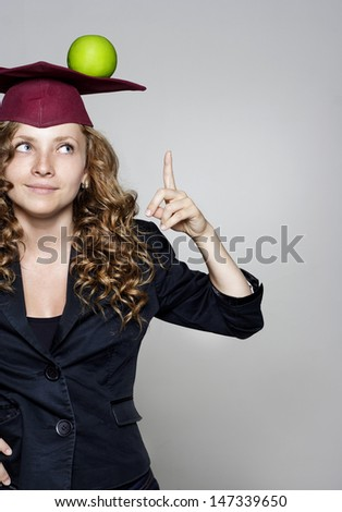 Young smiling caucasian student with an apple on her head - stock photo