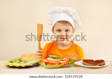 Young smiling chef at the table with ingredients is going to cook a hamburger - stock photo