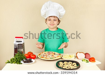 Young smiling chef in chefs hat enjoys a cooking tasty pizza