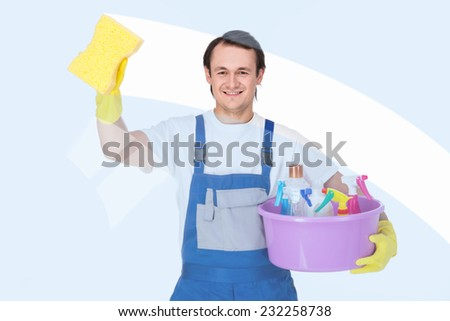 Young smiling cleaner man is cleaning windows on white background. - stock photo