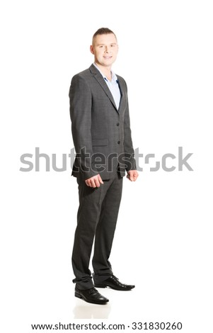 Young smiling confident businessman standing.
