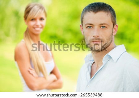 Young smiling couple against summer park. - stock photo