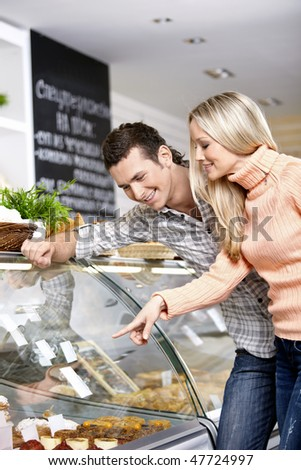 Young smiling couple at a shop show-window - stock photo