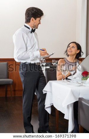 young smiling couple at the restaurant for dinner
