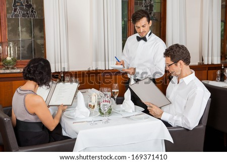 young smiling couple at the restaurant for dinner  - stock photo