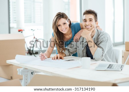 Young smiling couple designing their new dream house and smiling at camera - stock photo