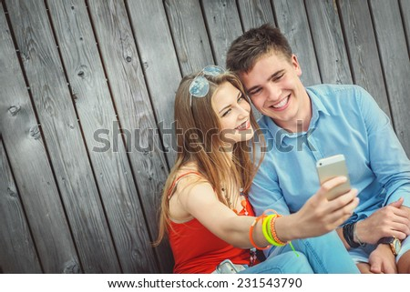 Young smiling couple doing selfie - stock photo