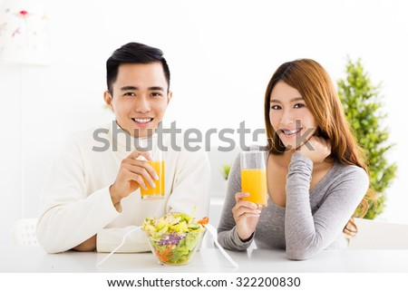 Young  smiling couple drinking juice and healthy food