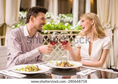 Young smiling couple enjoying the meal in gorgeous restaurant and drinking wine. - stock photo