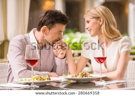 Young smiling couple enjoying the meal in gorgeous restaurant and drinking wine. Man kissing woman's hand. - stock photo