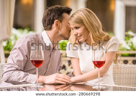 Young smiling couple enjoying the meal in gorgeous restaurant and drinking wine. Man whispering to woman. - stock photo