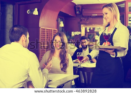 Young smiling couple having date in middle class restaurant. Focus on blonde girl
