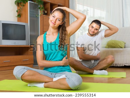 Young smiling couple having yoga class at home. Focus on girl  - stock photo