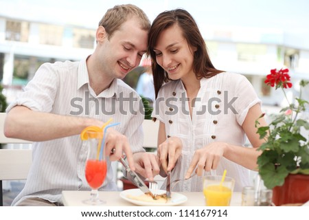 Young smiling couple in cafe - stock photo