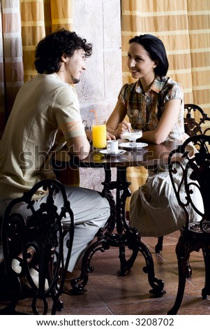 Young smiling couple in old cafe sitting at the table, talking, eating ice cream and drinking juice - stock photo