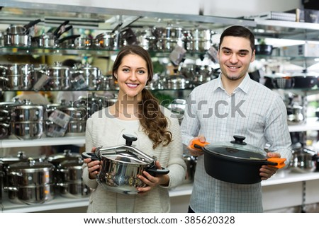Young smiling couple in supermarket choosing modern pans in kitchenware section. Focus on woman