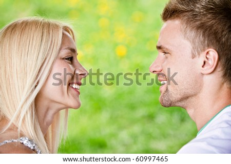 Young smiling couple look against each other and smile against summer park.