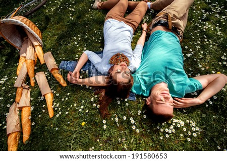 Young smiling couple lying and dreaming on the grass with basket and baguettes and flowers in their eyes, top view