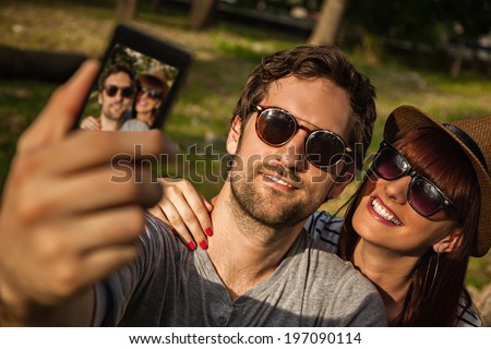 Young Smiling Couple Making A Self Portrait With Smart Phone. Focus Is On Couple. - stock photo
