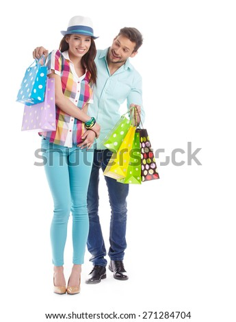 Young, smiling couple on a shopping spree. Shallow DOF, focus on woman's eye. - stock photo