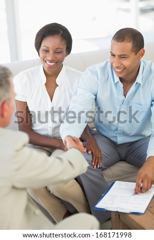 Young smiling couple shaking hands with salesman on the couch in the office