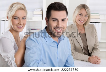 Young smiling couple sitting in a sales conversation at bank or insurance. - stock photo